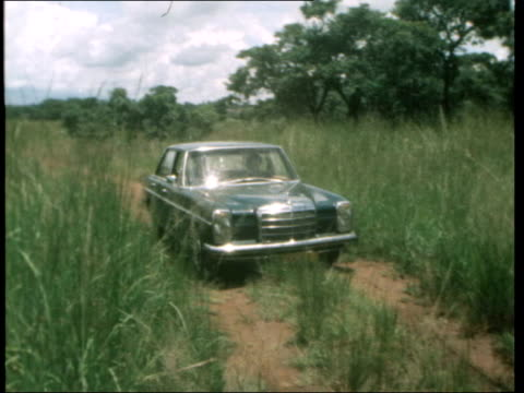 Rhodesians travel in convoys to avoid land mines RHODESIA TRACK From car through tall grass along Track TRACK Tarred road behind another car TS Hands...