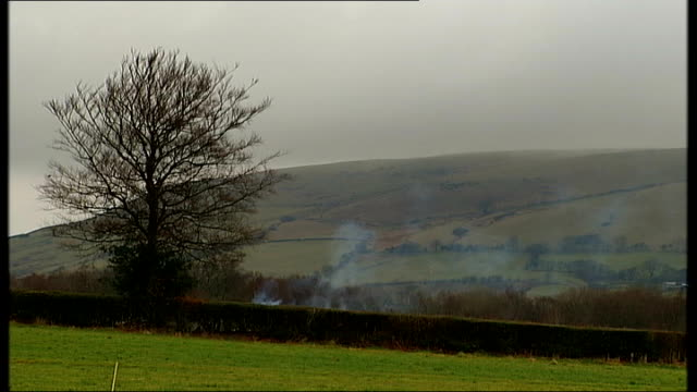 vídeos y material grabado en eventos de stock de rhondda valley: llantrisant: ext ioan glyn-cross set-up with reporter looking over countryside fileds and distant hills with gry clouds overhead ioan... - royal mint