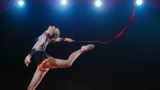 slo mo ld rhythmic gymnast doing a leap with her head leaned back while swirling her red ribbon - flexibility stock videos & royalty-free footage