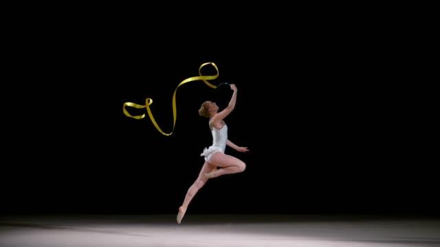 slo mo ld rhythmic gymnast doing a ribbon exercise running across the floor - rhythmic gymnastics stock videos & royalty-free footage