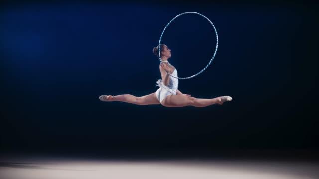 vídeos y material grabado en eventos de stock de slo mo ld gimnasta rítmica haciendo un salto dividido mientras rota un aro alrededor de su mano - perfección