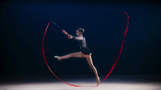 slo mo ld rhythmic gymnast doing a split leap while rotating a red ribbon in a wide circle - agility stock videos & royalty-free footage
