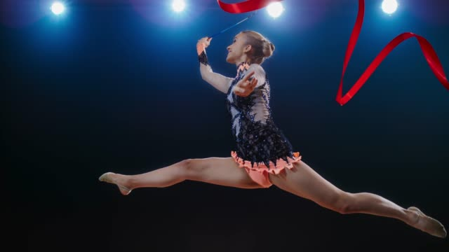 slo mo rhythmic gymnast doing a split leap with her red ribbon swirling in the air - rhythmic gymnastics stock videos & royalty-free footage