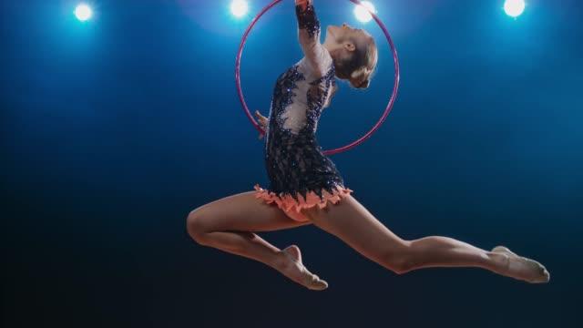 vídeos y material grabado en eventos de stock de slo mo ld gimnasta rítmica haciendo un salto de ciervo y girando su aro - competición