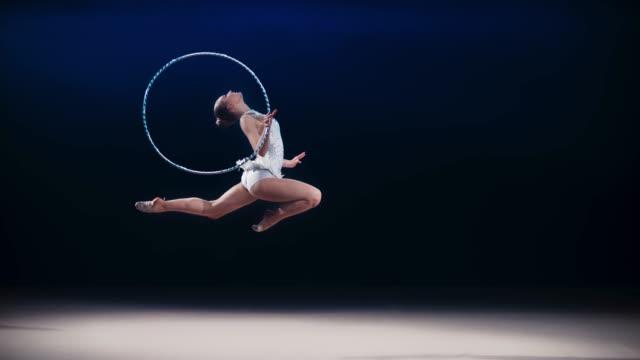 vidéos et rushes de slo mo ld gymnaste rythmique faire un saut de cerf tout en tournant un cerceau autour de sa main - pratique