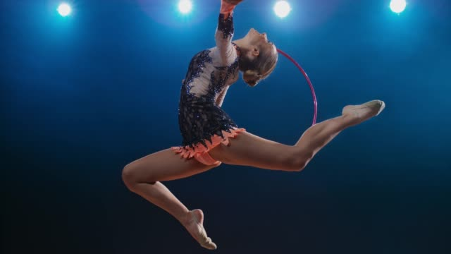 slo mo speed ramp ld rhythmic gymnast doing a stag leap with a hoop rotating around her hand - rhythmic gymnastics stock videos & royalty-free footage