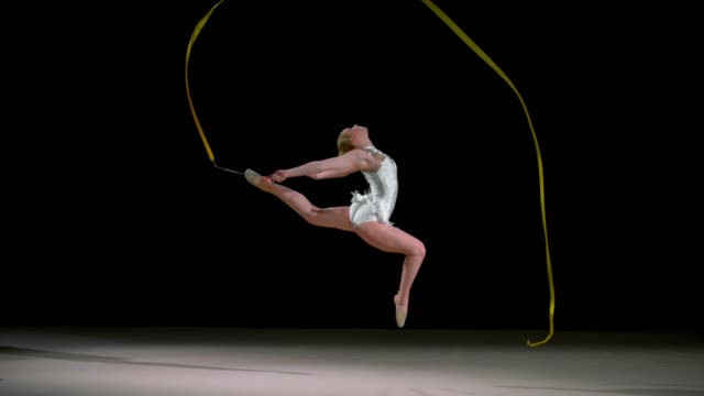 slo mo speed ramp ld rhythmic gymnast jumping while waving a ribbon across the air - accuracy stock videos & royalty-free footage