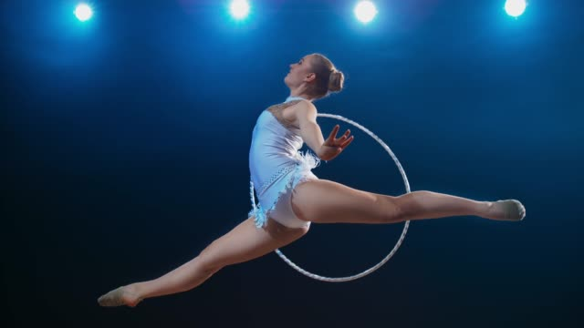 slo mo ld rhythmic gymnast performing a scissor leap while rotating her hoop - rhythmic gymnastics stock videos & royalty-free footage