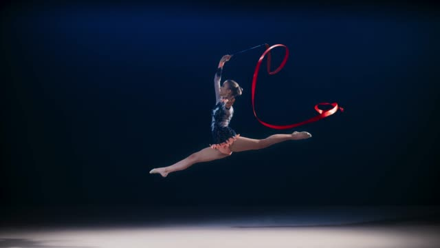 vídeos de stock e filmes b-roll de slo mo ld rhythmic gymnast performing a scissor leap while swirling a red ribbon above her - individualidade