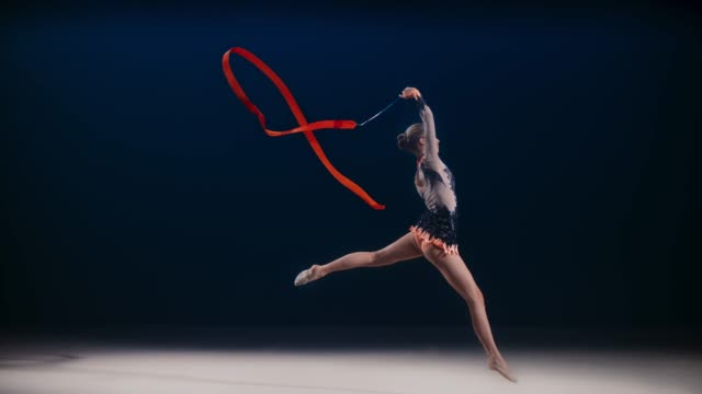 slo mo ld rhythmic gymnast performing a scissor leap while swirling a red ribbon - leotard stock videos & royalty-free footage