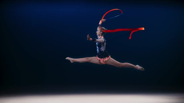 slo mo speed ramp ld rhythmic gymnast performing a split leap and swirling a red ribbon above her head - rhythmic gymnastics stock videos & royalty-free footage