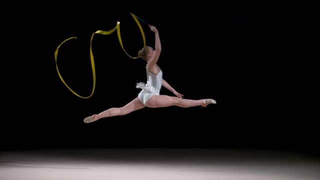 slo mo ld rhythmic gymnast performing a split leap holding a ribbon in her hand - televisione a ultra alta definizione video stock e b–roll