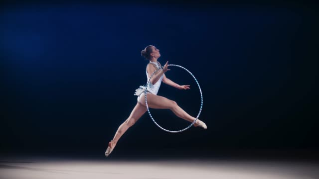 slo mo ld rhythmic gymnast performing a split leap while rotating a hoop in her hand - leotard stock videos & royalty-free footage