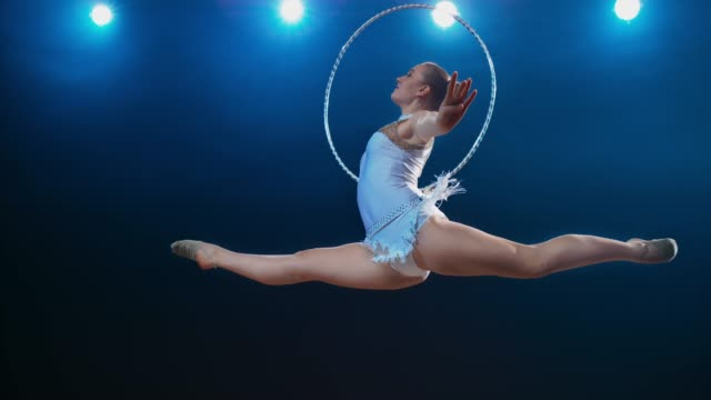 slo mo speed ramp ld rhythmic gymnast performing a split leap while rotating her hoop in one hand - leotard stock videos & royalty-free footage