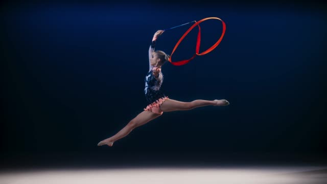 slo mo ld rhythmic gymnast performing a split leap while swirling a red ribbon - leotard stock videos & royalty-free footage