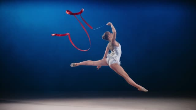 slo mo ld rhythmic gymnast performing a split leap while swirling a red ribbon - 18 19 years stock videos & royalty-free footage