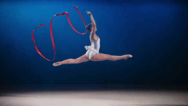 slo mo ld rhythmic gymnast performing a split leap with a red ribbon swirling in her hand - acrobatic activity stock videos & royalty-free footage