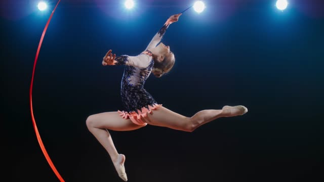 slo mo speed ramp ld rhythmic gymnast performing a stag leap while making a large circle with her red ribbon - skill stock videos & royalty-free footage