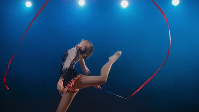 slo mo ld rhythmic gymnast performing a stag leap while making a large circle with her red ribbon - gymnastics stock videos & royalty-free footage