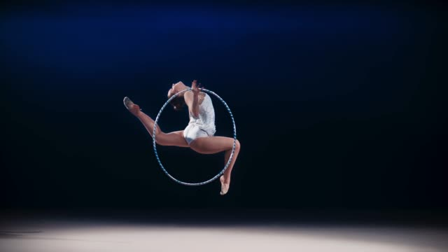 slo mo ld rhythmic gymnast performing a stag leap while rotating a hoop in her hand - leotard stock videos & royalty-free footage