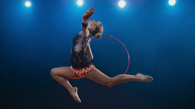slo mo ld rhythmic gymnast performing a stag leap while rotating her hoop - stage light stock videos & royalty-free footage
