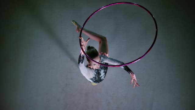 SLO MO LD Rhythmic gymnast rotating a hoop above her head while in a pivot