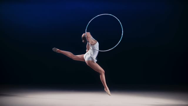 vídeos de stock e filmes b-roll de slo mo speed ramp ld rhythmic gymnast rotating a hoop around her hand during a stag leap - perfeição