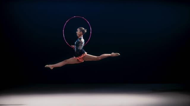 slo mo speed ramp ld rhythmic gymnast rotating her hoop and performing a split leap - black background stock videos & royalty-free footage