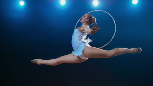 slo mo ld rhythmic gymnast rotating her hoop while performing a stag leap - leotard stock videos & royalty-free footage