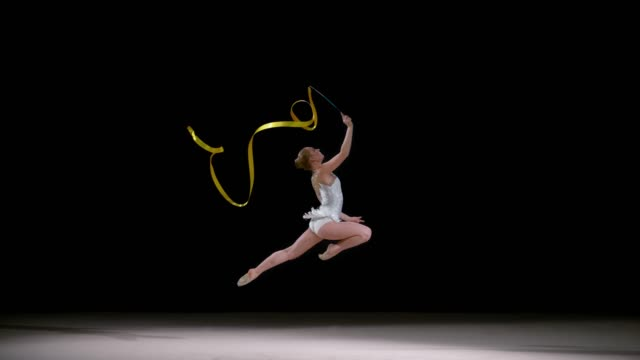slo mo ld speed ramp rhythmic gymnast running across the floor and swirling a ribbon - gymnastics stock videos & royalty-free footage