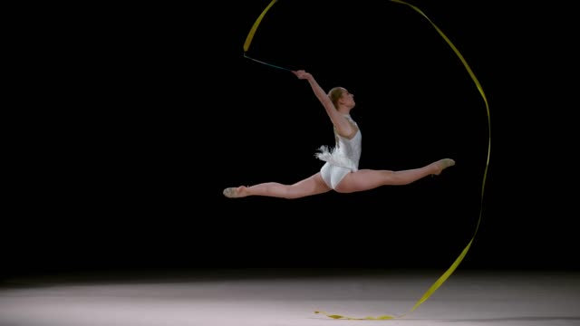 slo mo speed ramp ld rhythmic gymnast running across the floor doing a leap and swirling the golden ribbon - rhythmic gymnastics stock videos & royalty-free footage