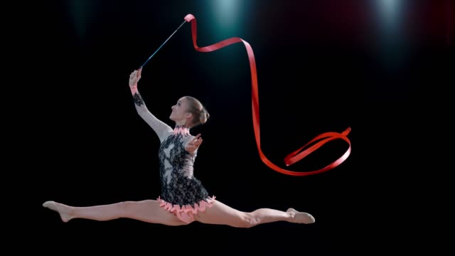 slo mo rhythmic gymnast smiling while doing a leap and rotating her red ribbon above her head - rhythmic gymnastics stock videos & royalty-free footage
