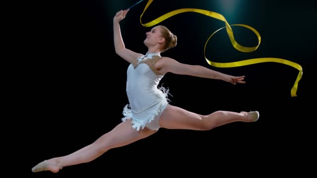slo mo rhythmic gymnast smiling while performing a split jump with a swirling golden ribbon - agility stock videos & royalty-free footage