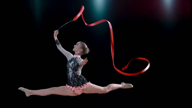 slo mo rhythmic gymnast smiling while performing a split jump with a swirling red ribbon - flexibility stock videos & royalty-free footage