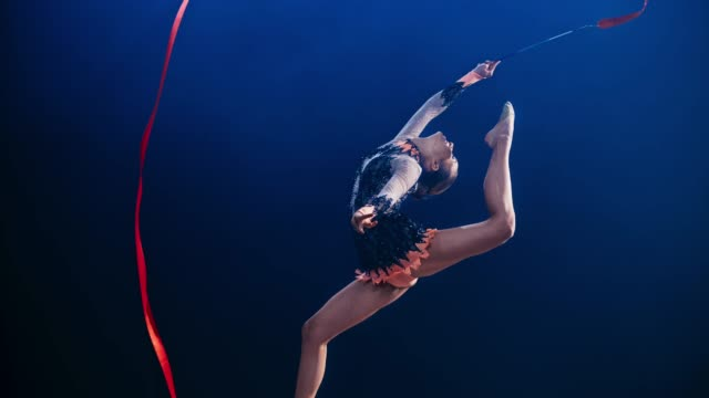 slo mo speed ramp rhythmic gymnast swinging her red ribbon above her head while doing a stag leap - flexibility stock videos & royalty-free footage