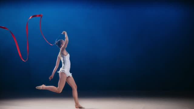 slo mo speed ramp ld rhythmic gymnast swirling a red ribbon above her head during a leap - leotard stock videos & royalty-free footage