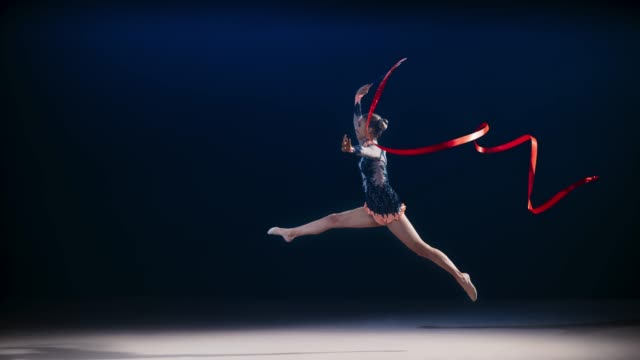slo mo rhythmic gymnast swirling a red ribbon and performing a split leap - perfezione video stock e b–roll