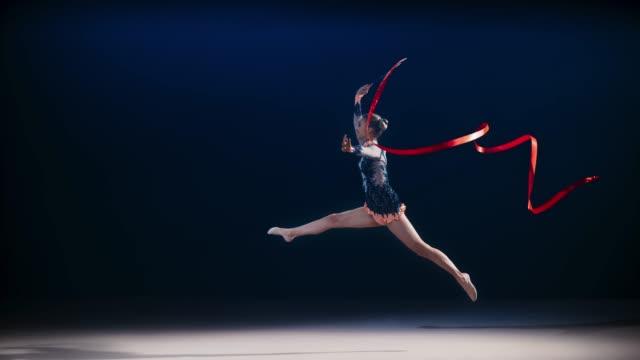 ginnasta ritmica slo mo che gira un nastro rosso ed esegue un salto diviso - super slow motion video stock e b–roll