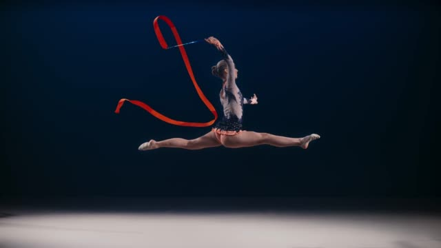 slo mo ld rhythmic gymnast swirling her red ribbon while performing a split leap - rhythmic gymnastics stock videos & royalty-free footage