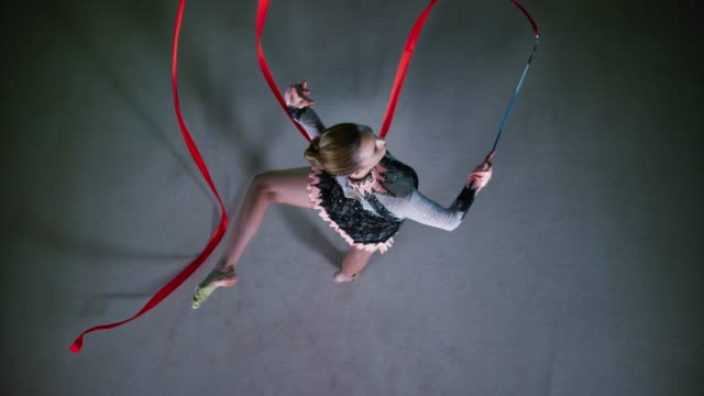 slo mo ld rhythmic gymnast swirling her red ribbon while performing the attitude pivot - flexibility stock videos & royalty-free footage