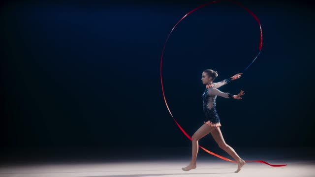 slo mo speed ramp ld  rhythmic gymnast waving a red ribbon and doing a split leap - perfection stock videos & royalty-free footage