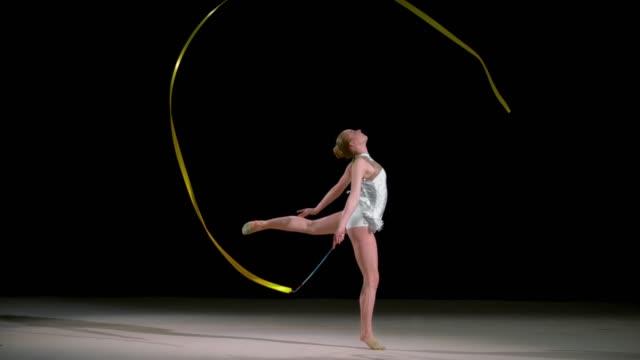slo mo rhythmic gymnast waving the ribbon in a circle while jumping - rhythmic gymnastics stock videos & royalty-free footage