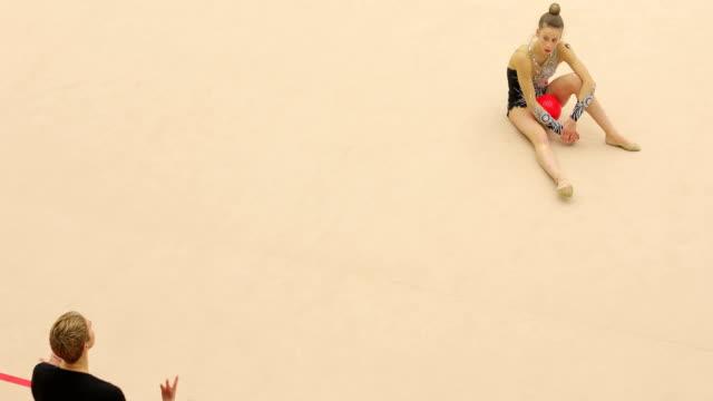 Rhythmic Gymnastics Coach Guiding Young Athlete Practicing