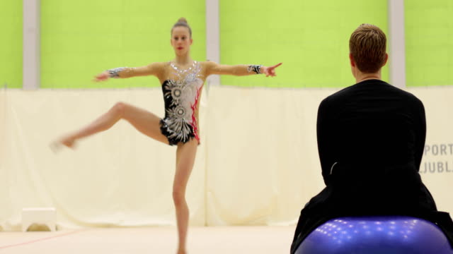 rhythmic gymnastics coach watching and guiding young athlete practicing - pirouette stock videos and b-roll footage
