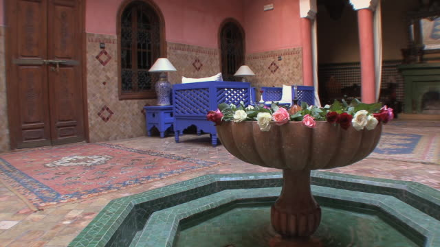 vidéos et rushes de ws pan riad courtyard with blue chairs and small pond, marrakech, morocco - palace