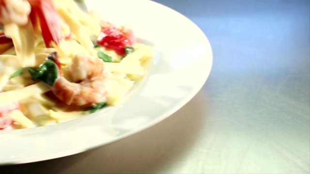 vídeos de stock, filmes e b-roll de ribbon pasta with prawns and cream sauce arranged on a plate - comida salgada