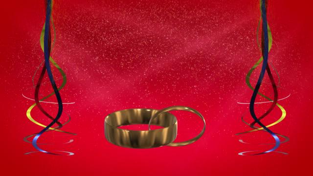 Anneaux d'or avec rubans et fond rouge boucle prêt