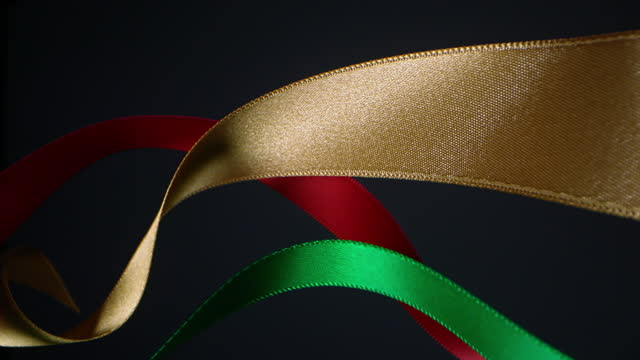 ribbons in christmas colors on black background, for celebration events and party for new year, birthday party, christmas or any holidays, waiving and curling in super slow motion and close up - loopable moving image stock videos & royalty-free footage