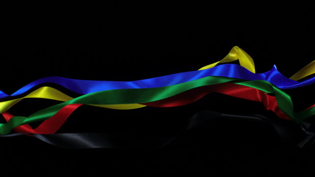 ribbons in olympic colors on black background, for celebration events and party for new year, birthday party, christmas or any holidays, waiving and curling in super slow motion and close up - loopable moving image stock videos & royalty-free footage