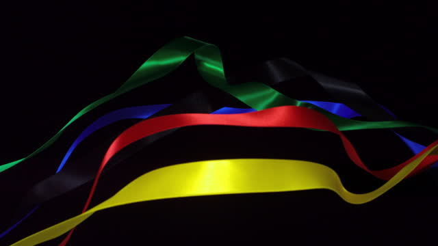 ribbons in olympic colors on black background, for celebration events and party for new year, birthday party, christmas or any holidays, waiving and curling in super slow motion and close up - satin stock videos & royalty-free footage